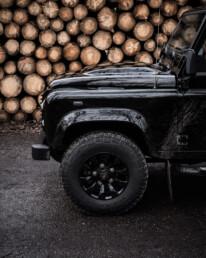 Land Rover Defender 110 Black Design Edition frontside in front of wood